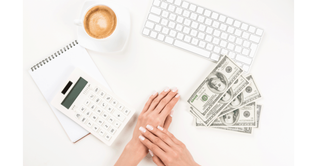 image of woman's hands resting on desk with calculator, keyboard, cash, and coffee